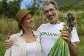 Couple of farmers showing onion — Stock Photo