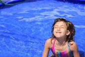 Child relaxing in pool sunbathing — Stock Photo