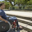 Man in wheelchair in front of stairs — Stock Photo #69294977
