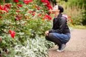 Young woman sniffing roses in a garden — Stock Photo
