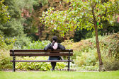 Girl sitting on a bench in a park — Foto Stock