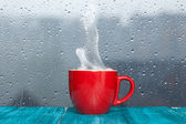 Steaming coffee cup on a rainy day window background — Stock Photo
