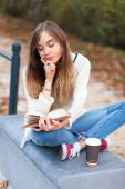 Young beautiful girl sitting on a bench in a park — Stock Photo