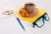 Coffee with croissant on a worktable — Stock Photo