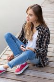 Young beautiful girl sitting on a pier — Stock Photo