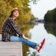 Young beautiful girl sitting on a pier — Stock Photo #57543737