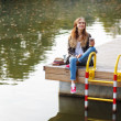 Young beautiful girl sitting on a pier — Stock Photo #57543773