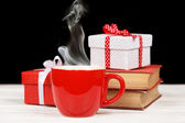 Steaming coffee cup with books and gift boxes — Стоковое фото