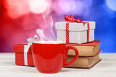 Steaming coffee cup with books and gift boxes — ストック写真