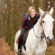 Young woman riding a horse — Stock Photo #58863125