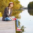 Young beautiful girl sitting on a pier — Stock Photo #64522489