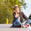 Young beautiful girl sitting on a pier — Stock Photo #64522511