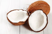 Cracked coconut on wooden table — Stock Photo