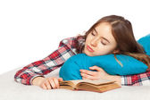 Young girl slepping with a book in bed — Stock Photo