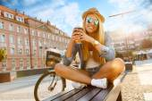 Young stylish woman with a bicycle in a city street — Stock Photo
