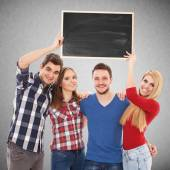 Group of happy young people with a blackboard — Stock Photo