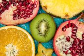 Colorful fruit slices on blue wood surface — Stock Photo