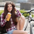 Young woman drinking coffee on a bicycle trip — Stock Photo #70262093