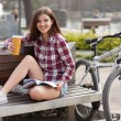 Young woman drinking coffee on a bicycle trip — Stock Photo #70262511