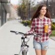 Young beautiful woman with coffee cup and a bicycle — Stock Photo #70262803