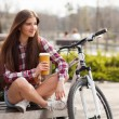Young woman drinking coffee on a bicycle trip — Stock Photo #70937927