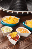 Plate of nachos with different dips — Stock Photo