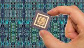 Microprocessor in hand in front of chip layout — Stock Photo