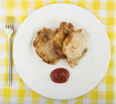 Fried pork cutlet, tomato sauce in plate on tablecloth — Stock Photo