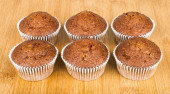 Six muffins in row on wooden board — Stock Photo
