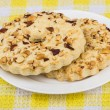 Two shortbreads rings with peanuts in plate on yellow tablecloth — Stock Photo #73315307