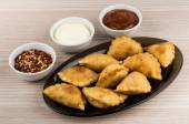 Pasties in dish and bowls  with spices on wooden table — Stock Photo