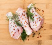 Three chicken legs sprinkled pepper on wooden board — Stock Photo