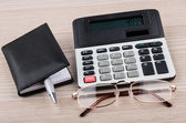 Calculator, notepad, pen and glasses on table — Stock Photo