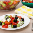 Transparent glass bowl and plate with Greek salad, fork — Stock Photo #74781617