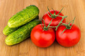 Ripe red tomatoes on branch and cucumber on board — ストック写真