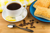 Coffee, pieces of lemon and sugar, plate with flaky biscuits — Stock Photo