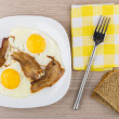 Fried eggs and bacon in glass plate, fork on napkin — Stock Photo #79299288