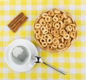 Small bread rings in basket, tea and sticks of cinnamon — Stock Photo