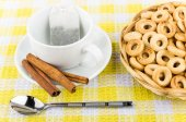 Packet of tea in cup, cinnamon and small bread rings — Stock Photo