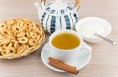 Bread rings in wicker basket, tea, cinnamon, teapot and sugar — Stock Photo