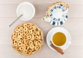 Small bread rings in basket, tea, sticks of cinnamon, teapot — Stock Photo