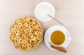 Small bread rings in wicker basket, tea, sticks of cinnamon — Stock Photo