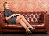 Woman on sofa with notebook — Stock Photo