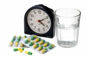 Pills with glass of water and alarm clock — Stock Photo