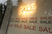 Sale poster in the display window of shop — Foto Stock