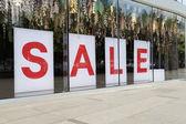Sale poster in the fashion shopfront — Stock Photo