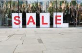 Sale poster in the fashion shopfront — Stock Photo