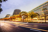 Modern office building and traffic trails in urban city — Stock Photo