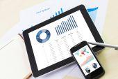 Digital tablet e smartphone com relatório financeiro gráfico — Fotografia Stock