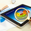 Hand with magnifying glass above the tablet with financial chart report — Stock Photo #63120373